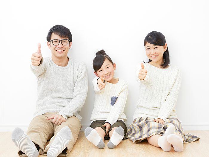 床に座って親指を立てる家族